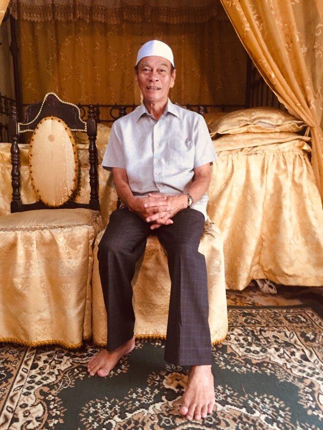 """Ibrahim """"Hadji"""" Mushim dans la villa Sentosa, devant un lit ancien. © Claude Hudelot"""