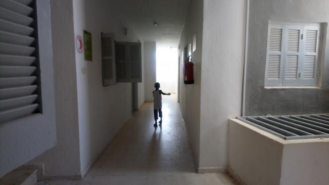 Un niño juega en los pasillos del centro controlado por la OIM. © Lilia Blaise