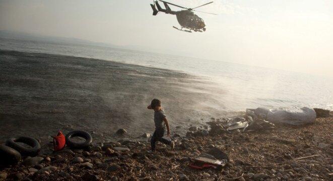 Août 2015 : un hélicoptère de l'agence Frontex décolle au-dessus d'un enfant syrien qu'il vient de déposer sur l'île grecque de Lesbos. © Antonis Pasvantis / Reuters