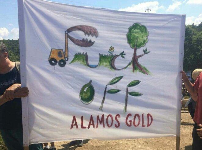 Mont Ida : Banderole dénonçant la responsabilité de la compagnie canadienne Alamos Gold dans la destruction de l'environnement