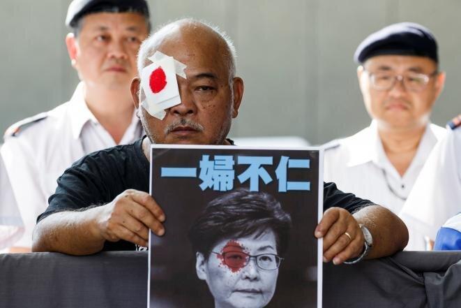 Un manifestante denuncia la violencia policial con un retrato de la jefa del Gobierno Carrie Lam. © Reuters