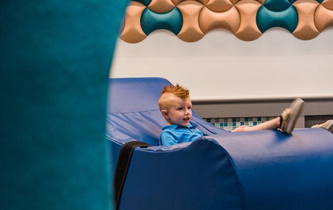 Presley Rudge, un enfant autiste de 4 ans, essaie l'un des fauteuils à bascule souples de la salle des sens. La chaise est livrée avec une sangle de sécurité pour éviter les chutes. © Avec l'aimable autorisation de l'aéroport international de Pittsburgh.