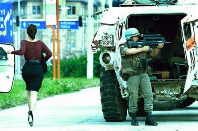 """Un casque bleu à Sarajevo tente de couvrir une femme sur """"Sniper alley"""" le 4 août 1994"""