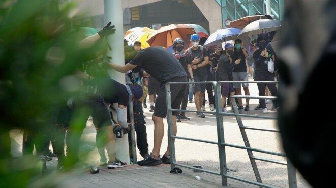 """Les manifestants tentent de faire un """"parapluie bloc"""" pendant qu'un des leurs coupe à la disqueuse un lampadaire équipé de caméra. Hong Kong le 24/08/2019. © Pierre Thomas"""