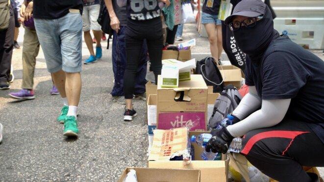 Un manifestant masqué distribue gratuitement des bouteilles d'eau le long du parcours de la manifestation. Hong Kong le 24/08/2019. © Pierre Thomas