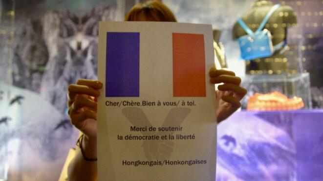 """Les manifestants ont recrée une """"Baltic line"""" durant une heure. L'une d'entre elle appelle la France. Central Hong kong le 23/08/2019 © Pierre Thomas"""