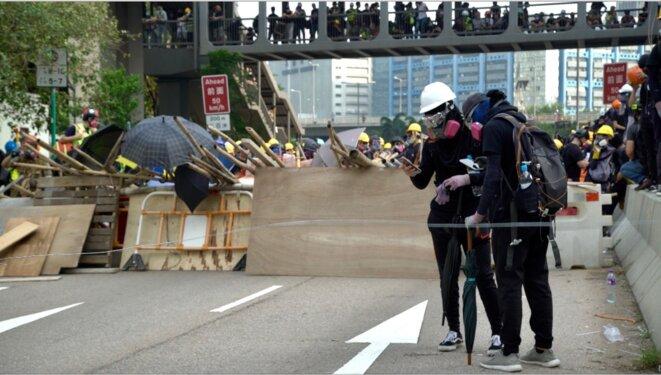 Les manifestants ayant monté des barricades regardent leurs smartphones en attendant les sommations de la police. Hong Kong le 24/08/2019 © Pierre Thomas