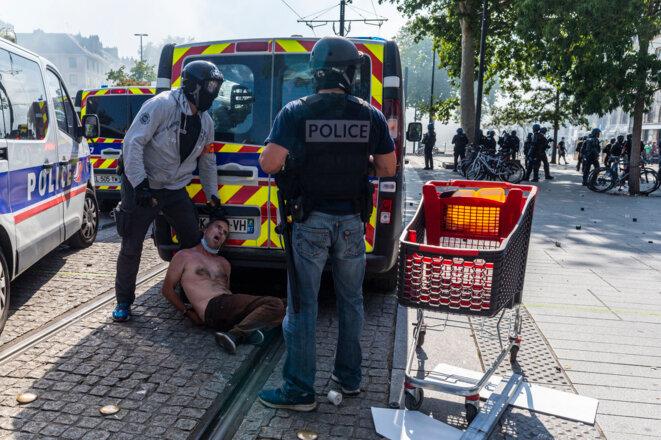Photo de Bruno Kaïk, derrière les fourgons de police, entouré de policiers de la BAC, le 3 août, à Nantes. © Greg Looping / Hans Lucas