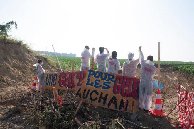 Le 26 juin 2019, des opposants à la gare promise par le gouvernement aux promoteurs d'EuropaCity déploient une banderole « Une gare pour les gens, pas pour Auchan » © Sophie Deiss