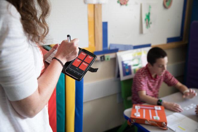 Pour le compte rendu :  Un chercheur enregistre les comportements de chaque enfant dans une application pour smartphone. © Erin Little