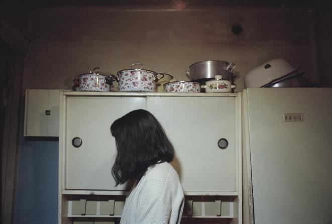 Olessia Venediktova, Brunette woman with pots in the background, Tbilissi, Georgia, 2015, From the series Forget Them © Olessia Venediktova