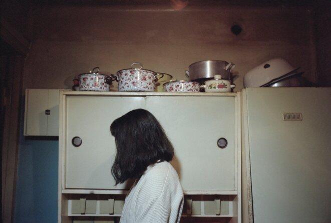 Olessia Venediktova, Brunette woman with pots in the background, Tbilisi, Georgia, 2015, from the series Forget Them © Olessia Venediktova