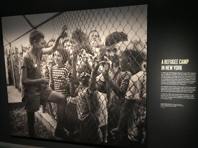"""Un camp de réfugiés, Fort Ontario, à New York, en 1944 : """"un jeune réfugié s'entretient avec un groupe d'enfants américains à travers la clôture entourant le refuge d'urgence"""""""