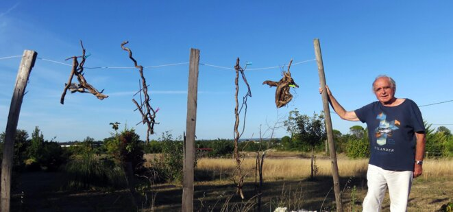 Jean Maureille et une partie de l'installation « Linge éphémère », branches suspendues avec objets divers, piquets et corde, 2019