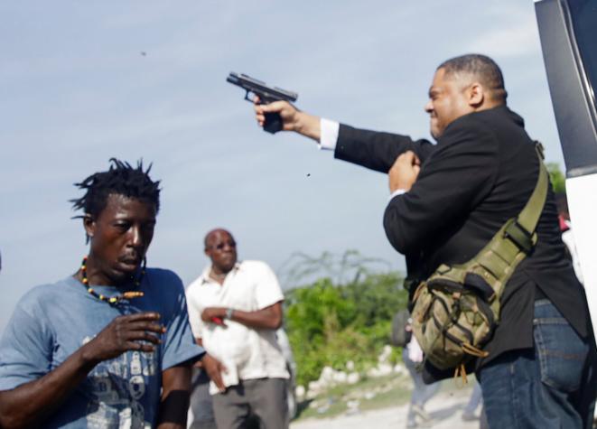 Le sénateur Jean-Marie Ralph Fethière tirant sur des manifestants, le 23 septembre. © Reuters