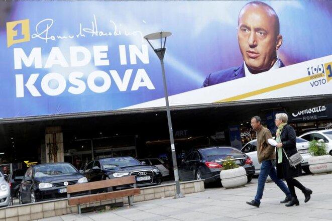 Des passants devant une affiche de Ramush Haradinaj à Pristina (Albanie), le 4 octobre 2019. © REUTERS/Florion Goga