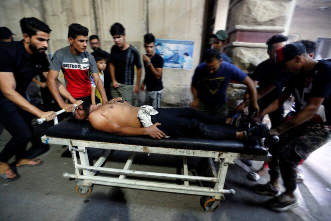 Un manifestant blessé est évacué vers l'hôpital après avoir été blessé, le 5 octobre, à Bagdad, lors d'un défilé anti-gouvernemental. © Reuters