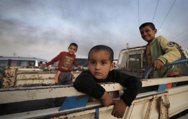 Des enfants dans un camion fuyant la ville de Ras al-Ayn, le 9 octobre 2019. © Reuters