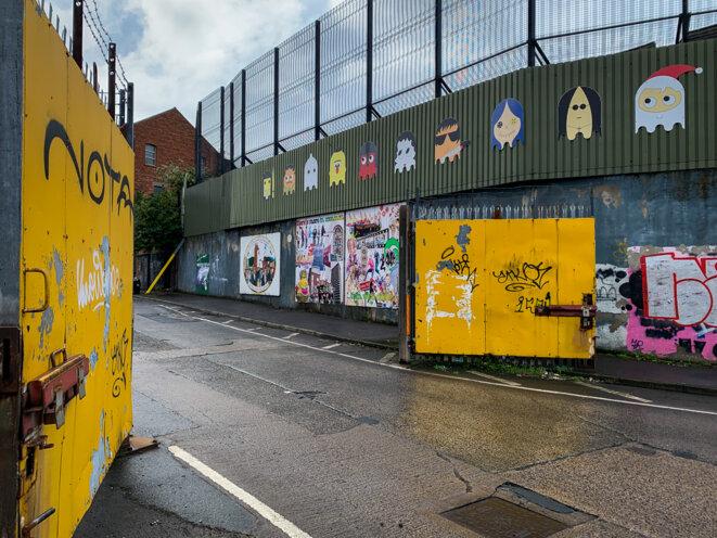 Le mur et une des portes de séparation entre catholiques et protestants à Belfast, désormais ouverte. © Thomas Cantaloube