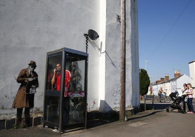 Graffiti en una pared frente a una cabina telefónica, cerca de la sede del servicio de inteligencia electrónica, el GCHQ, en Cheltenham, al oeste de Inglaterra, el 16 de abril de 2014. Una obra del artista callejero Banksy que ilustra las revelaciones de Edward Snowden, quien declaró que el GCHQ había utilizado cables de fibra óptica que transportaban las comunicaciones internacionales y el tráfico de Internet para desviar cantidades ingentes de datos personales. © Reuters/Eddie Keogh