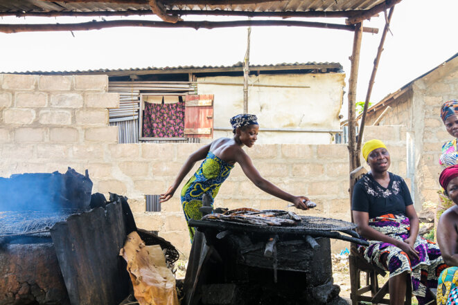 Une femme fait fumer du poisson avant d'aller le vendre au marché central de Porto Novo.