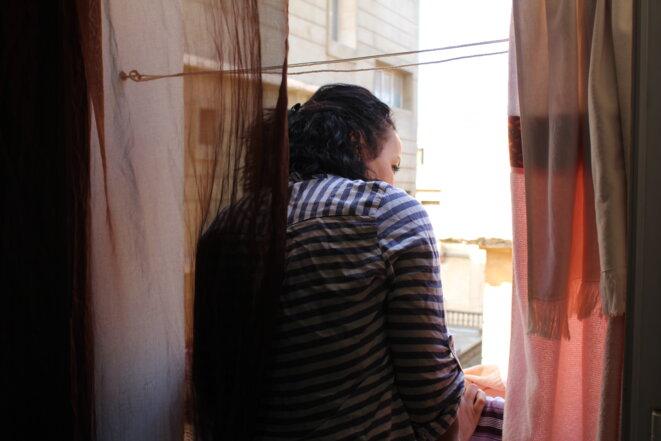 Samia, 39 ans, jette un œil par la fenêtre de son appartement, dans le quartier de Miramar à Oran. © NB