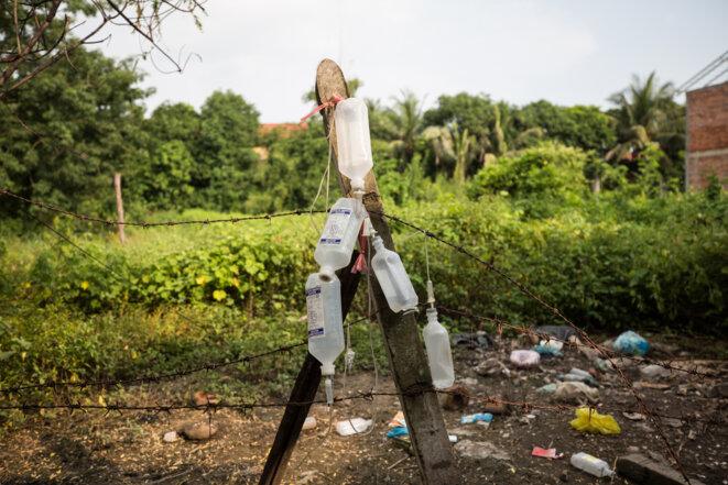 À l'arrière de la maison de la famille Piseth, les bouteilles de solutions pour perfusion intraveineuse qui ont servi pendant cette saison aux membres de la famille infectés par la dengue à s'auto-soigner. © Luke Duggleby