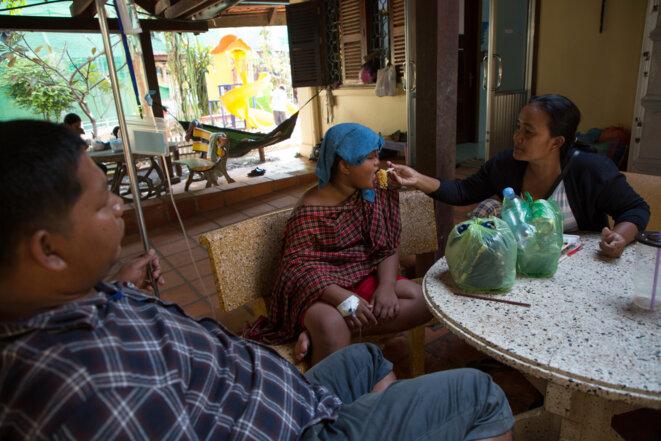 Dans la cour de l'hôpital pour enfants d'Angkor, le couple Piseth nourrit son fils, qui se remet d'une forme sévère de dengue hémorragique. La réhydratation et une nutrition équilibrée sont une part importante du processus de guérison. © Luke Duggleby