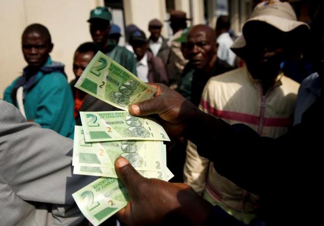 Un homme présente les nouveaux billets de deux dollars à l'extérieur d'une banque à Harare, le 12 novembre 2019. © REUTERS/Philimon Bulawayo