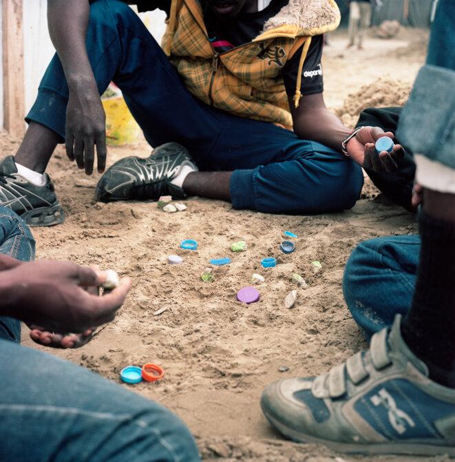 Gilles Raynaldy, 9 mai 2016 – Des jeunes Soudanais jouent au jeu du Dalla, zone nord, image issue du journal Welcome my friend, 2016, réalisée dans le cadre d'une commande publique photographique du Centre national des arts plastiques (Cnap) et du Pôle d'Exploration des Ressources Urbaines (PEROU) intitulée « Réinventer Calais », FNAC 2018-0398 (1), Cnap © Gilles Raynaldy / Cnap