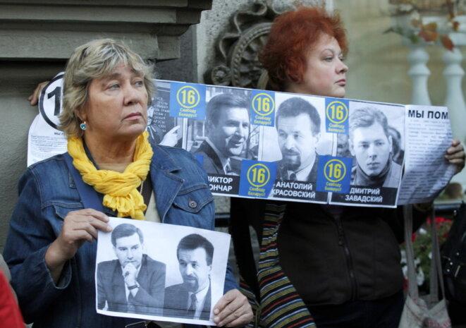 Manifestants avec des portraits de Gonchar et Krasovsky lors d'un rassemblement de l'opposition à Minsk. © EPA