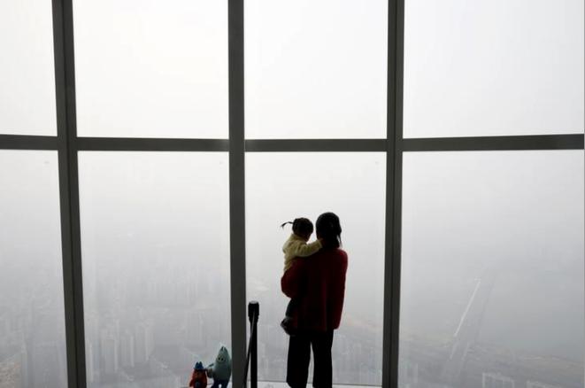 Une femme portant son bébé regarde la ville de Séoul plongée dans un épisode de pollution en mars 2019. © REUTERS