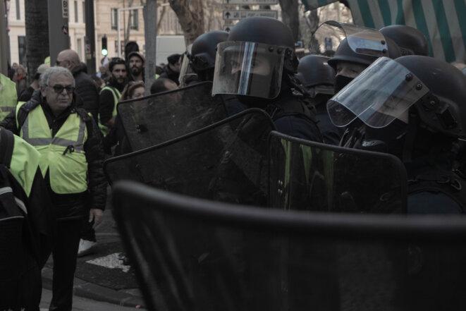 Le cortège des Gilets Jaunes et des syndicats, encadré par les forces de l'ordre. © Justin Carrette