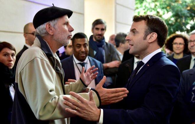 Le professeur de mathématiques Pierre Coste discute avec Emmanuel Macron de sa réforme des retraites à Pau, le 14 janvier. © Reuters