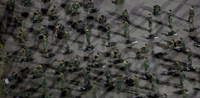 La police paramilitaire chinoise se tient debout sur la place du Peuple où des centaines d'Ouïghours ont commencé une manifestation qui a éclaté en émeutes en juillet 2009. Cinq ans plus tard, la Chine a commencé à emprisonner des Ouïghours dans des «hôpitaux de rééducation». (AP Photo / Ng Han Guan)