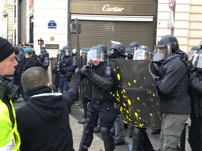 A police officer takes aim with a rubber bullet weapon during a 'yellow vest' protest in Paris, December 8th 2018. © Karl Laske