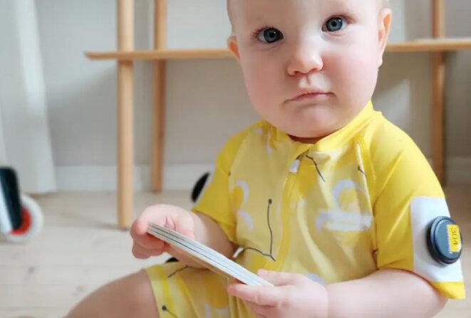 Un bébé dans un pull jaune équipé de capteurs de suivi des mouvements © Spectrum News