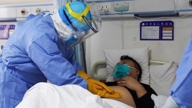 un membre du corps médical examine un patient infecté par le nouveau coronavirus dans un pavillon d'isolement d'un hôpital à Zouping, en Chine, dans la province de Shandong à l'est de la Chine, le 28 janvier 2020