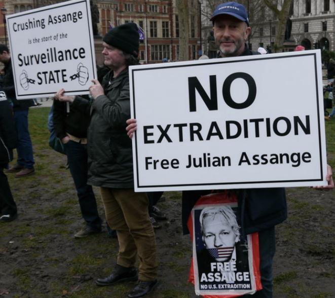 """En la manifestación en apoyo de Julian Assange el sábado 22 de febrero en Londres. En la pancarta de la izquierda: """"Aplastar a Assange es el comienzo del estado de vigilancia"""". La pancarta de la derecha dice: """"No hay extradición. Libere a Julian Assange"""". © Jérome Hourdeaux"""