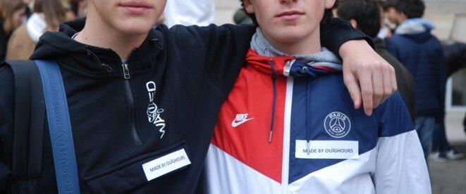 """Deux jeunes lycéens posant avec l'étiquette """"made by Ouïghours"""""""