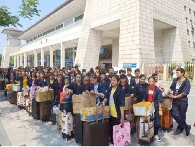 Des travailleurs ouïghours de la société Hubei Yihong Precision Manufacturing Co. Ltd lors de leur transfert entre le Xinjiang et Xianning, Hubei. Cette photo a été prise devant la gare de Wuchang à Wuhan, la capitale provinciale de Hubei, en mai 2018.
