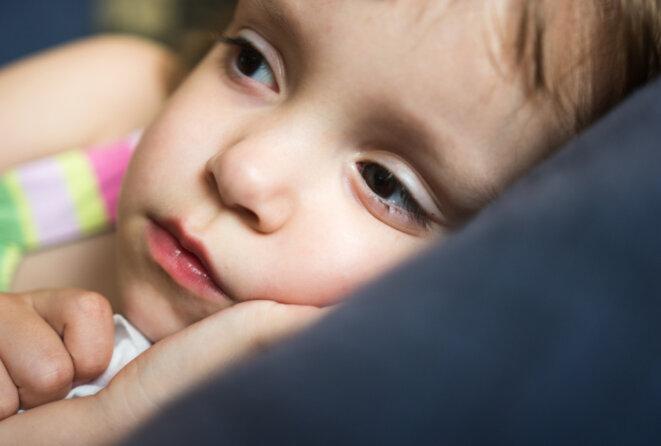 Une petite fille allongée et éveillée © Marizza / iStock