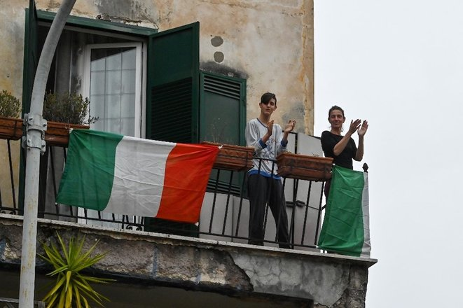 14 mars 2020. À Rome, de jeunes gens sur leur balcon applaudissent en chantant. Un appel lancé sur les réseaux sociaux a suggéré aux Italiens de chanter tous à la même heure pour sortir de l'isolement lié aux précautions face au Covid-19. © Andreas Solaro / AFP