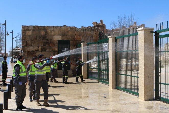 Des soldats libanais désinfectent l'entrée du site historique de Baalbek le 16 mars 2020. © AFP
