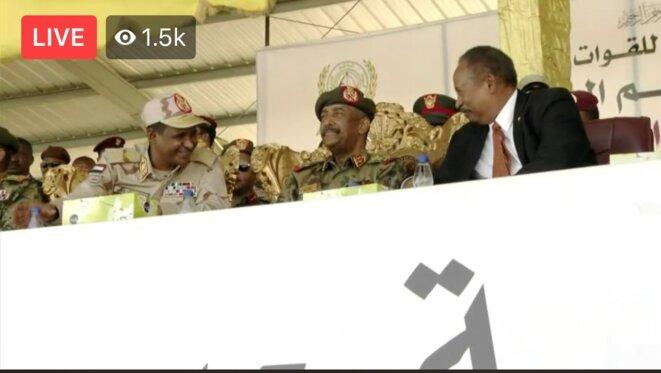 Le Premier Ministre Abdalla Hamdok et le Chef des RSF Hemetti s'amusent et blaguent ensemble pendant la cérémonie des RSF du 7 mars 2020. Capture d'écran de la retransmission vidéo de la cérémonie.