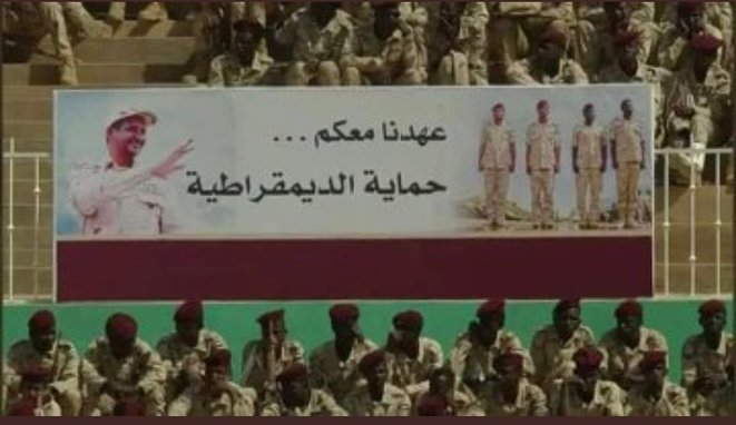 """Bannière lors de la cérémonie de fin de formation des recrues des Forces de Support Rapide le 7 mars 2020. """"A vos côtés.. Pour protéger la démocratie""""."""
