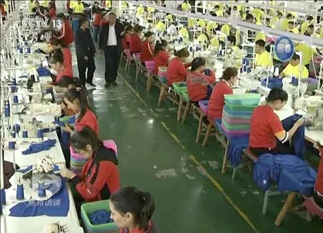 Capture d'écran du reportage de la télévision chinoise CCTV des «stagiaires» de ces camps travaillant dans une usine de confection. /Associated Press
