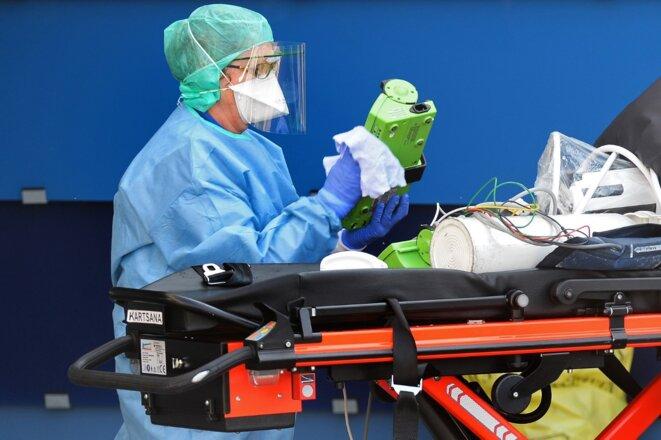 Une infirmière désinfecte le matériel d'une ambulance ayant transporté un patient atteint de coronavirus, le 24 mars 2020. © Jean-François MONIER / AFP