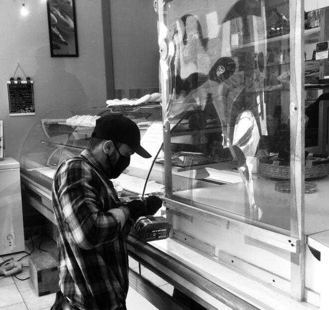 Un militant associatif installe une protection en Plexiglas dans une boulangerie à Cosne-Cours-sur-Loire (58) © Julie Déléant