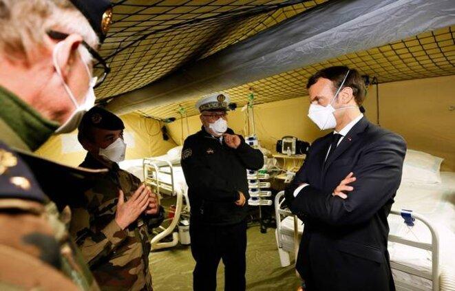 Emmanuel Macron, avec un masque, visitant l'hôpital militaire de campagne déployé à Mulhouse, le 25 mars. © AFP
